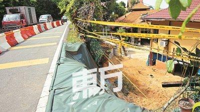 公共工程局周三已使用防崩布覆盖土崩的山坡,为了驾驶人士安全,峇都丁宜路暂已关闭一条车道,预计修复工程将耗费3至4周才完成。(摄影:蔡开国)