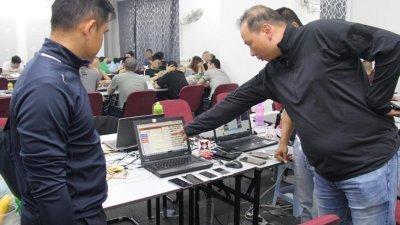 扎菲尔(右)和下属检查网络赌博集团成员所使用的笔电。