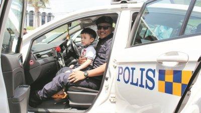 一名孩童在警员的陪伴下,体验乘坐警方巡逻车到邻近社区巡逻。