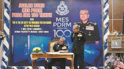 """弗兹(左)在出席仪式后,为吉隆坡总警长拿督斯里玛兹兰所购买的""""警察100周年特刊""""签名留念。"""
