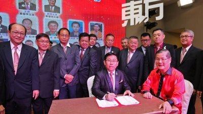 李文发(坐者左起)签署巴西古当华团联合会新届理事就职书。郑金财见证。前排站者左为姚文春。(摄影:刘维杰)