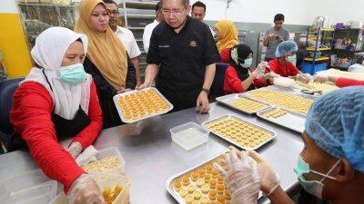 沙拉胡丁(左3)参观黄梨加工食品工厂时,了解黄梨饼的制作。(摄影:刘维杰)