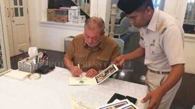 柔佛苏丹依布拉欣陛下(左)在开斋节贺卡上签名。
