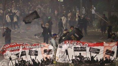 印尼军警22日晚间用催泪瓦斯强力驱离发动暴力攻击的群众,群众不愿退去,挥舞旗帜像是在向警方示威。
