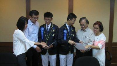 谭永翔(左3起)和程俊里向各自的父母展示得奖证书。左起为曾华斌、谭家隆、程家强和李丽萍。(摄影:黄俊南)