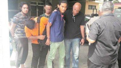 图为反恐组警员正将2名嫌犯铐上手铐,押解回总部接受调查。
