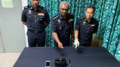 阿都阿兹(中)在建功警官的陪同下,向媒体展示嫌犯所使用的凶器,及死者遗物;右为本案查案官蔡汉伦助理警监。