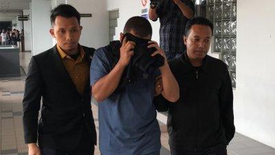 莫哈末哈纳菲(中)被反贪会官员带离法庭时,以黑色外套遮脸,避免样貌曝光。