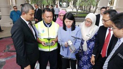 杨美盈(左3)向官员了解无人机的运作。左为萨鲁丁嘉玛,左4为慕妮拉。