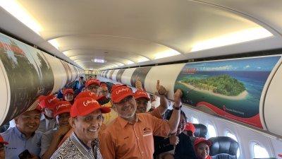 卡立沙末(右)推介亚航客机机舱上的的纳闽景点广告。