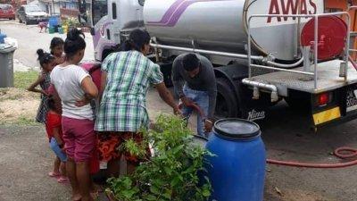 水务公司派出水槽车到受影响的地区派水,居民正准备提水。