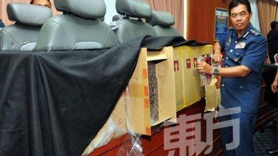 莫哈末哈密丹展示起获的66万5720令吉走私香烟,以及暗藏走私香烟的客货车椅背。(摄影:杨金森)