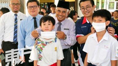 沙哈鲁丁(后排左3)和杨敦祥(后排右)为小学生戴上口罩,左起为莫哈末礼查和陈加福。(摄影:杨金森)