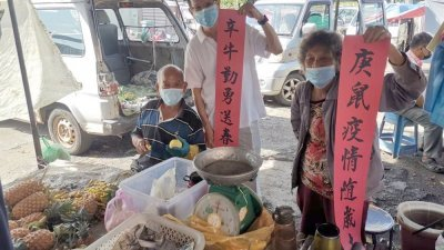颜和财(左2)在英丹园市集赠送春联给一对小贩,春联寓意对美好充满期待。