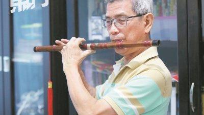 覃友习得笛子多年,虽未曾表演,却仍非常钟爱吹奏笛子。(摄影:刘维杰)