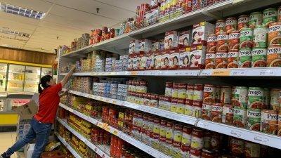 市面上的罐头食品货源充足,一名超市员工在进行日常的补货工作。