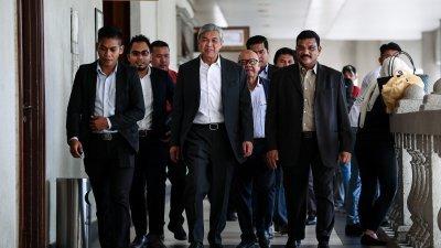 阿末扎希(中)在支持者陪同下,到吉隆坡法庭出席其案件的审讯。