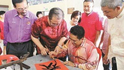 常受邀在各大小场合示范书法的萧志远(左2),曾在去年的活动上邀请已故的莫哈末法立为其挥写的春字,补上最后一划。