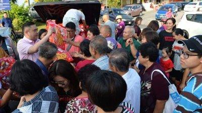 """""""我的交通部长来了""""!市民一窝蜂涌向陆兆福(左)索取福袋及福字装饰。"""