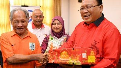 依丁沙里(右)赠送年柑给予瓜拉庇劳的华裔选民,提早向他们贺年。