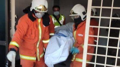消拯员在灭火后,抬出死者遗体。
