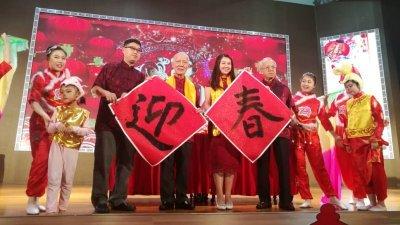 何朝东(左4起)及廖彩彤在书法家的陪同下,挥毫写下迎春二字。
