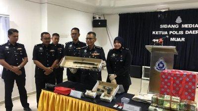 查哈鲁丁(左5)展示警方起获的手枪、子弹、武士刀和毒品。