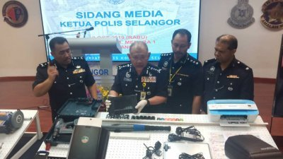 雪州总警长拿督诺阿占(左2)曾在去年10月召开记者会,向媒体记者展示偷车集团所使用的高科技盗车工具。(档案照)