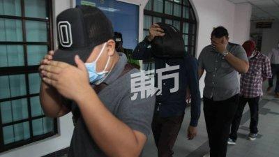 4名被告步入法庭时以手掩脸,闪逃摄影镜头。