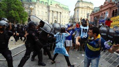阿根廷足球传奇马拉多纳当地时间周三因心脏病逝世,灵柩暂放总统府供民众入内瞻仰,但部分球迷周四不耐排队久候,在府外街头与镇暴警察爆发冲突,警方还向民众挥动警棍。(图取自路透社)