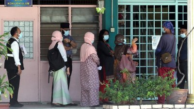 卫生局官员到学校进行观察,并为曾跟疑似确诊学生有近距离接触的师生进行病毒检测。