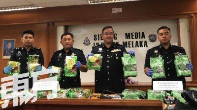 祖基菲里(右2)及警官展示毒贩以茶袋为掩饰的冰毒。