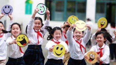 """江苏省扬州市汶河小学的学生们在""""笑迎世界微笑日""""活动中手举笑脸卡做游戏。"""
