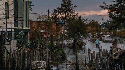 """飓风""""艾达""""于上周日登陆美国路易斯安那州后造成严重灾情,图为吉恩拉菲特社区被洪水淹浸,一名居民在洪水中穿过后院向外求救。(图取自法新社)"""